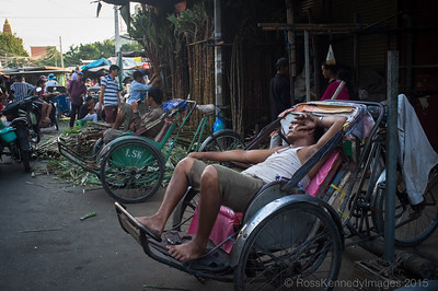 Exhausted Cyclo drivers wait to pick up sugar cane