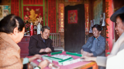 Yang Zheng Qi (l) and Yang Wen Hu (r), both 73, playing majong at the hidden courtyard.  Natural light, tilt shift