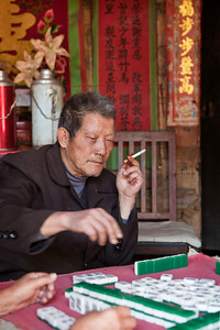 Mahjong Player  Yang Zheng Qi, 73, playing majong at the courtyard.    Natural light