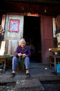 Woman preparing onions in the courtyard  Yang Qing Gu, 73, prepares onions on the doorstep of her Xizhou home.  Natural light