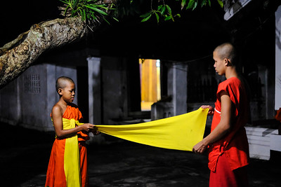 Elder monk helps a novice with his robe as they prepare for morning alms collection, Wat Syrimoungkoun Xaiyaram, Luang Prabang