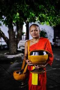 A monk waits with the Abbot's collection pot, Wat Syrimoungkoun Xaiyaram, Luang Prabang