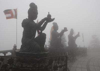 three smaller statues surrounding the Tian Tan Buddha on Lantau Island, Hong Kong, China