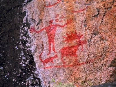 "North Hegman Pictographs.  The arrangement of figures at the main panel of the North Hegman Lake, Minnesota rock art site appears to have been carefully composed at one time by one rock artist. Its present excellent condition suggests either that it may not be especially old or that it is a site where an older pictograph has been repainted. The rock art appears to represent Ojibwe meridian constellations visible in winter during the early evening, knowledge of which may have been useful for navigating in the deep woods during the winter hunting season. Support for a suggested multi-layered interpretive model comes from a review of various culturally specific ethnohistorical sources. The inclusion of elements from widely known Ojibwe legends and references to constellations with cosmological or religious significance make it an intriguing scene with many interesting culturally specific referents. This panel is perhaps the most visited and photogenic pictograph within the State of Minnesota and it possesses remarkable artistic merit.    Some of the best known and most photographed pictographs in the Upper Midwest are located at North Hegman Lake, northwest of Ely, MN, in the Boundary Waters Canoe Area Wilderness on a granite cliff overlooking the water. This rock art is located within the ""northern woodlands"" stylistic rock art region of Campbell Grant (1983) and Klaus Wellmann (1979).  The panel shows a human figure in an outstretched arms posture standing near a quadruped animal with a long tail, possibly a dog or wolf, and a remarkably well drawn bull moose with splayed hooves and dew claws. (A dew claw on a moose is a reduced hind toe or the false rudimentary hoof above the true hoof .) Beneath these figures is a long horizontal line, probably representing the ground or horizon, and above the human figure are two vertical rows of short horizontal lines or dashes. One set has 4 lines and next to it are 3 lines. Above and to the right are what look like three canoes. The top two canoes have two paddlers and the third has a faint single one in the middle. Above the moose's rack is a single mark. Above all of these figures is a large cross like a ""plus"" sign.  Several feet to the left of the scene are other much more faint pictographs including 6 horizontal lines, one above the other, three crosses above each other, and a ""Y"" shaped figure with a ""C"" shape to it with diagonal strokes. There may also be a spiral and grid-like figure near the water.  The arrangement of figures at the main panel of the North Hegman Lake, Minnesota rock art site appears to have been carefully composed at one time by one rock artist. After examining the pictographs from about a foot away, it appears that the application of the red ochre was relatively recent, since it hardly looks weathered compared to other similar red ochre pictographs in northern Minnesota. It is also possible that someone has carefully reapplied ochre to a much older pictograph.  Although experiments have shown that red ochre on a rock face can become sealed through natural processes and remain quite bright even when very old, I saw no particular indication from looking at the panel up close that it was naturally encapsulated or sealed; however, I have not viewed it under magnification nor conducted any sort of microscopic examination of the surface.  The most likely candidates for the cultural groups who were making red ochre pictographs with these kinds of figures during the historical period were the Ojibwe and Cree. Other similar sites in the region have been investigated by researchers like Thor Conway (1993), Selwyn Dewdney and Kenneth Kidd (1973), Henry R. Schoolcraft (1851), Grace Rajnovich (1994) and others. Most of the other recent red ochre pictographs in this area appear to have been made by Ojibwe individuals who were recording shamanistic dreams and visions and Ojibwe leaders who were recording their biographical exploits.  The panel's anthropomorphic figure is painted with an ""outstretched arms"" posture rather than an ""upraised arms"" posture. Henry R. Schoolcraft, an Indian Agent whose wife was half Ojibwe and whose mother-in-law was a full-blood Ojibwe, authored a multi-volume work called Historical and Statistical Information . . . of the Indian tribes of the United States published in 1851. According to Schoolcraft, in pictographic inscriptions used in hunting, an anthropomorph with upraised and outstretched arms ""depicts a Meda [shaman]. He is about to open his performances, and appeals to the candor and sympathy of his fellows."