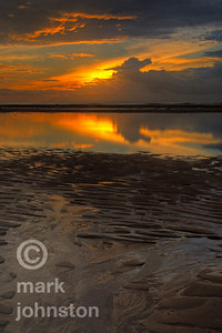 Sunrise at Sanur on the southeast coast of Bali. At low tide in this area, water draining off the beach leaves interesting shapes in the foreground, while a shallow lagoon inside the surf line reflects the distant clouds and brightening sky.