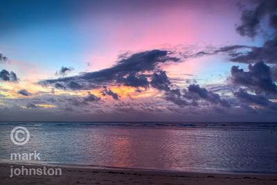 Sunrise at Sanur on the southeast coast of Bali near high tide. Solid cloud cover to the east obscured the sunrise, except for a short period where a band of pink shot up from behind the clouds, illuminating the morning sky and announcing the arrival of Sol.