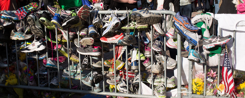 Running shoes left by mourners are part of the Boston Marathon bombing victims memorial in Boston's Copley Square - April 25, 2013