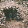 Carl Bumann looks in dugout where miners lived.   Stove and beds were still inside.  Schwab miners camp.  Death Valley NM, California.  1973