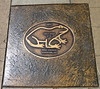 A bronze plaque is placed in the Angels Camp sidewalk for the winner of each year's frog jump competition at the Calaveras County Fair.