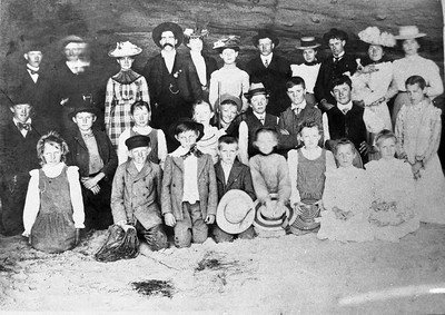 Beach picnic in about 1906.  Top row from left is Alwin Roeben, Alwin Wiegand, Elizabeth Wiegand, John hall, Kate Schiller, Florence Cole, Mr. Reed, Alice Hauck, Walter Hauck, Hattie Cole and Mrs. Reed.  Center row from left is Harry Yager, Frank Reseck, Emma Groh, Myrtle Yager, Herman Wiegand (with what appears to be a shotgun), John Teten, Louise Weller, Charley Cole, Edna Hauck.  Bottom row from left is Minnie Groh, Albert Lickert (with coil of seaweed), Gerhert Cole, Fritz Wiegand, Maud Yager, Emma Yager, Alwine Hauck and Amelia Wiegand.  Location is Seaside beach in Solona Beach.