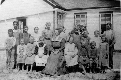 Olivenhain school class of 1907.  Back row from left is Gerhart Cole, Bruno Denk, Alwine Hauck, Amelia Wiegand, Marie Bumann, Alex Reseck, Ludwig Denk, Marie Teten and Freddie Reseck.  Front row from left is John Reseck, Lauise Bumann, Anna Bumann, Agnes Reseck, Kate Schiller (teacher), Laura Bumann, Louise Reseck, Aloys Waltz and Anna Denk.  Location is southwest corner of 7th street and Cole Ranch road.