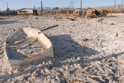 Bombay Beach was once a thriving resort that included boat docks, piers, yacht club, motels and more.   It is now a bleached and abandoned wasteland.  Location is on east shore of Salton Sea, 14 miles north of Niland .