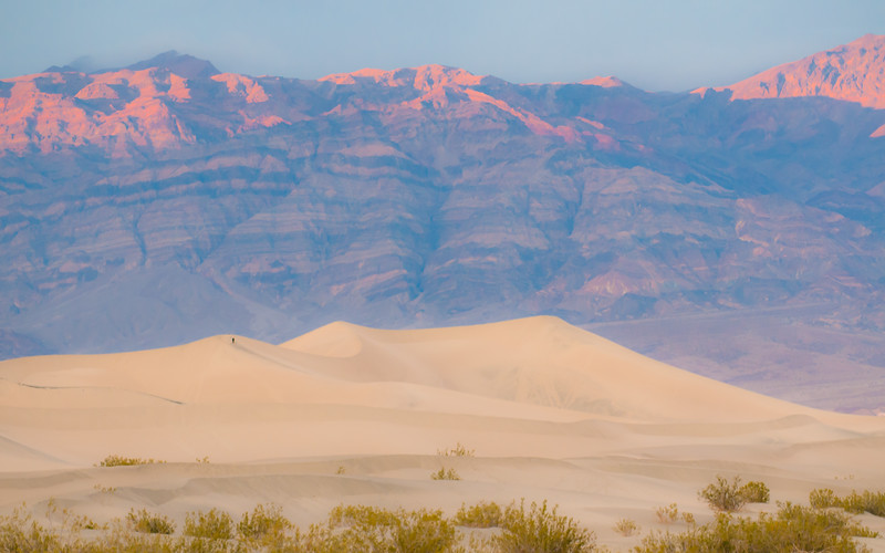 The person descending from the left summit of the sand dune gives you an idea of the scale. The mountains beyind rise 6,000 feet above the valley floor.