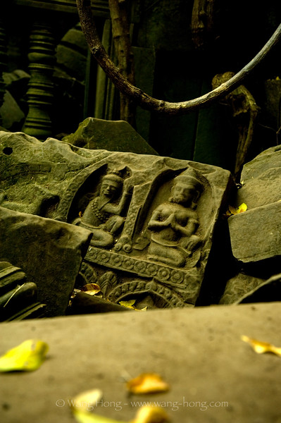 Buddha figures on a fallen stone in the jungle, at Beng Mealea.