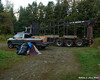 The log truck with the new building supports on it and the pickup with the start of the first load of trash
