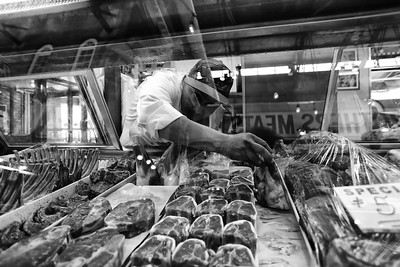 A worker packs cuts of meat in a display case at St. Lawrence Market in Toronto, Canada