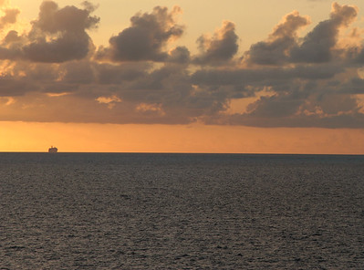 A ship sits on the horizon at sunset