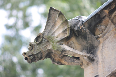 A gargoyle made of stone on the corner of an old building