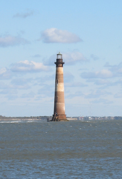 <b>Morris Island Light</b> - The lighthouse you see today is the third to occupy this site. It stands 158 feet tall and housed a 1st Order Fresnel Lens. It began operation in 1876 and was originally 2700 feet inland. It is now 1600 feet offshore and the closest viewpoint is at Folly Beach.