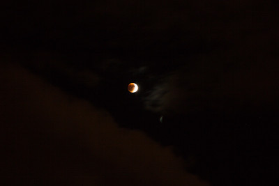 Red moon emerges from clouds
