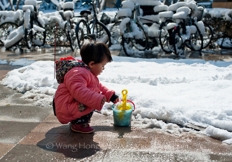 Little girl playing with snow.