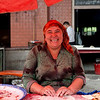 A happy lady making baked dumplings on street of Kashgar