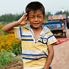 Boy posing for photos in the field of snow chrysanthemum outside City of Kashgar, Xinjiang.