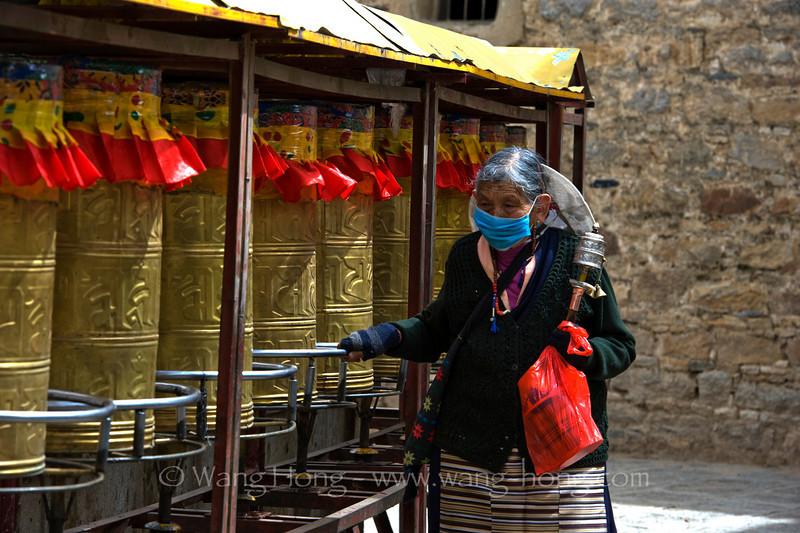 Turning the prayer wheels outside Drepung Monastry