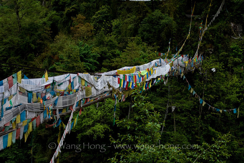 Suspension bridge lined with prayer flags over Yarlung Tsangpo River in east Tibet.