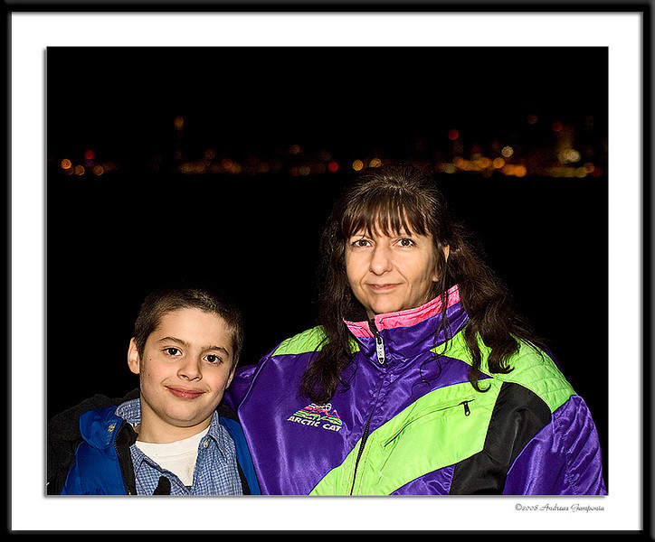 "Rennie and her son Ben.  This was in the evening as we were preparing to board the decorated Official Christmas Ship Spirit of Seattle, leading the Christmas Ship parade from downtown Seattle's dock 55, decked out in colorful lights and Christmas pageantry for the Festival of Lights Christmas Ship tour of the Seattle harbor and local area.  A local featured choir on the ship sings 20-minute programs at scheduled shoreside locations. The choir is broadcast over state-of-the-art speaker systems, letting those on shore join in the festivities. Onboard, Santa mingles with guests, spreading cheer. Certain holiday activities keep guests entertained between choral performances: sing-a-longs, a ""Ho-Ho-Ho"" contest, a children's activity corner, and the camaraderie that the holiday spirit brings out."