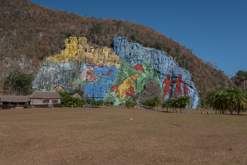 Spanning from early mollusks and other ancient sea-organisms, the rock face mural moves through the age of the dinosaurs, and ends with three giant red human figures. Both lauded as brilliant in its simplicity, and decried as an eyesore, it has taken a massive effort from the community to maintain the mural after the death of its creator.
