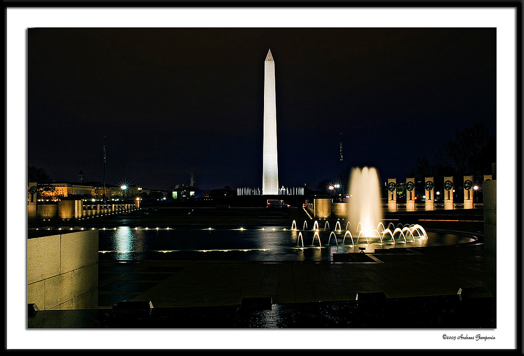 "This photo was taken above the waterfall of the freedom wall of the World War II Memorial looking towards the brighly lit scene of the National Monument.  To the right and left, hidden on a small section of wall is a historic enscription: ""Kilroy was here"""