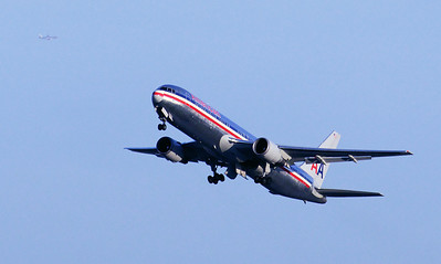 An American 767 tucks in the gear shortly after takeoff, with another jet in the background.