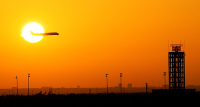A jet passes through the sun landing at DFW, just after sunrise.