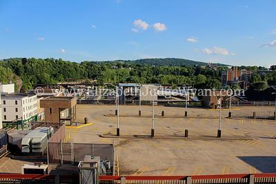 Old parking garage in foreground, new parking garage construction underway.