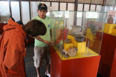 Roni, our tour guide at Agua Blanca, explains some of the artifacts on display in the museum to Deb.