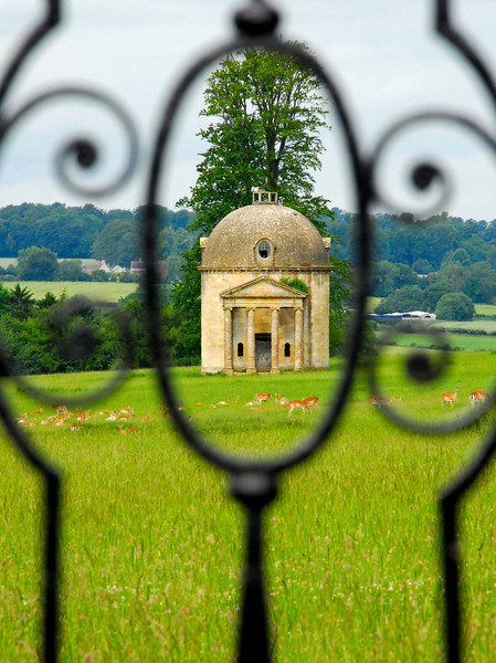 Estate pavillion and deer herd through wrought iron fence - Barrington, England
