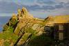 Man enjoying view atop rock formation near stone house - Polperro, England