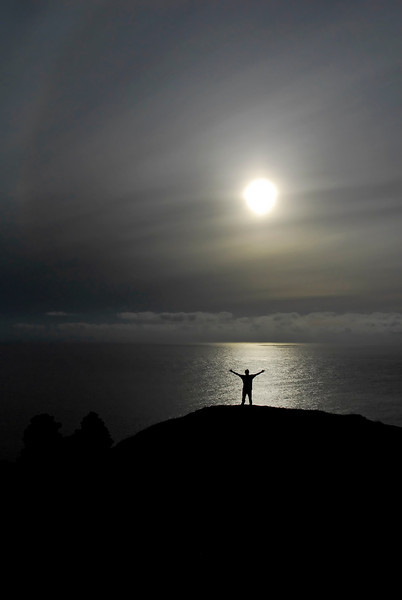 Silhouette of man with arms raised on hilltop at sunset - Botallack Tin Mines, England
