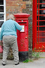 Woman posting letter in red English post office box - Avebury, England