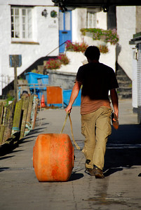 Worker walking a giant boat bumper in Cornwall - Clovelly, England