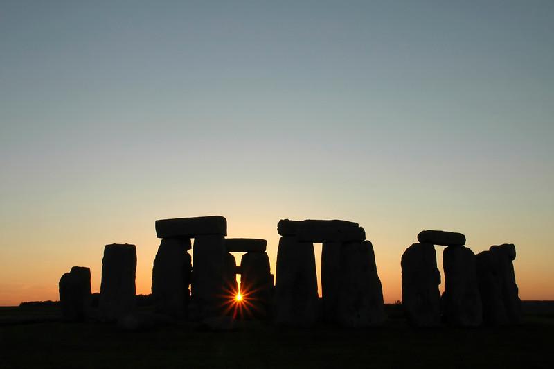 Stonehenge silhouette at sunset with sunburst - England