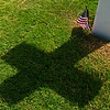 Cross shaped shadow cast by a grave marker at the American Cemetary in Normandy, France. A small American flag is at the base of the grave marker.