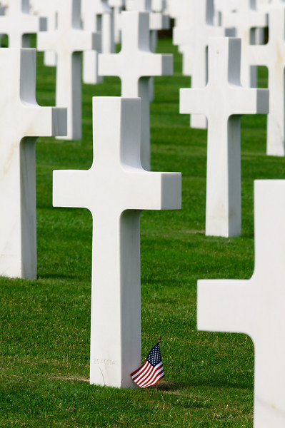 Closeup of crosses in the American Cemeter in Normandy, France. A small American flag is at the base of one of the grave markers.