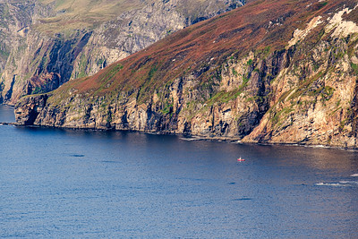 A fishing boat at the base of the cliffs at Slieve League