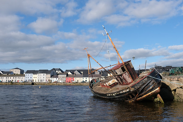Wrecked fishing boat resting at low tide in Galway.