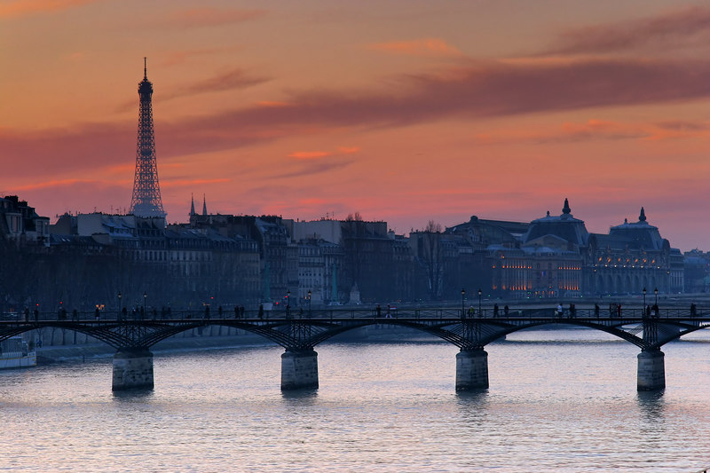 """From near Notre-Dame the scene of La Seine and La Tour Eiffel was stupendous. The sunset managed to squeeze through the cold dreary gray.<br><br><span class=""""subcaption"""">For the sunset shots I drew my thick scarf into a pile and set up a camera holder on the pedestrian handrail overlooking the river.</span>"""