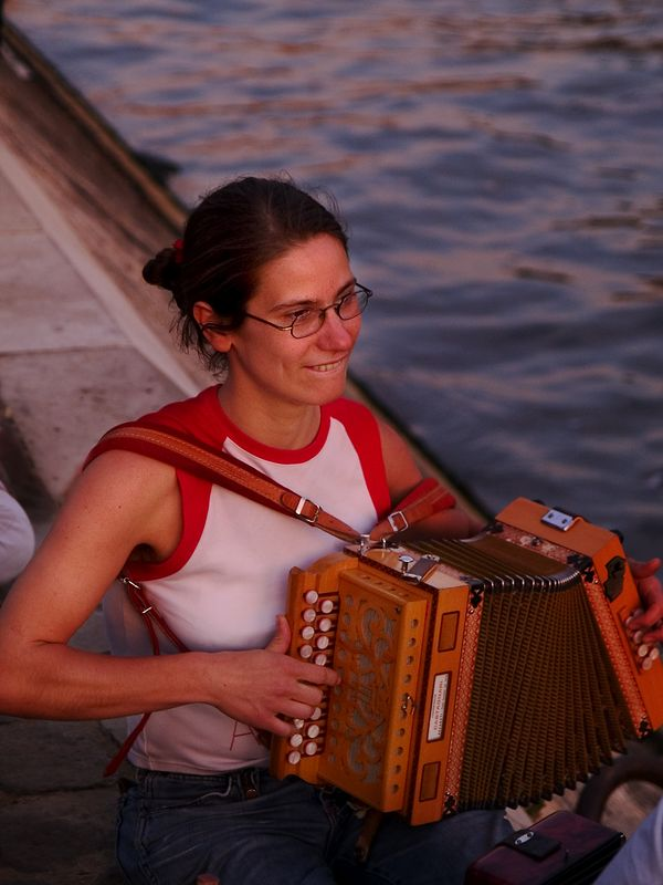 """Concertina musician ( <a href=""""http://www.concertina.net"""">http://www.concertina.net</a>) near the Pont Neuf (French for 'New Bridge') the oldest bridge in Paris. It is also Paris' best known bridge.  The Pont Neuf actually consists of two different bridge spans, one on each side of the Ile de la Cité, where the Vert-Galant square connects the two spans. (21 Jun 05)"""