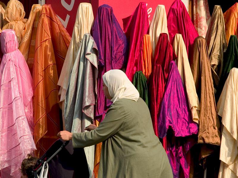 A shopper passes by the silk on the Boulevard de Rochechouart, Montmartre, Paris, France, 20 June 05.