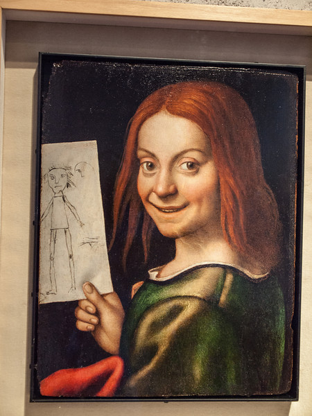 """Portrait of a Child with a Drawing, by Giovanni Francesco Caroto (1480 – 1555 or 1558), an Italian painter of the Renaissance active mainly in his native city of Verona.  <br /> <br /> In the official museum website there is the following description:  """"John with Drawing of a Clown by Francesco Caroto (Verona, 1480 - circa 1555). It is a portrait, remarkable for the presence of the childlike drawing, that documents the influence on Caroto of Leonardesque works seen during his stays in Milan.""""<br /> <br /> He initially apprenticed under Liberale da Verona (1445-1526/1529), a conservative painter infused with the style of Mantegna. Caroto after a stay in Milan, began responding to the other influences from Francesco Bonsignori, Leonardo da Vinci, Raphael, and Giulio Romano; but he never lost a certain individuality and his rich Veronese color. He is perhaps best known for having trained, along with the younger Antonio Badile, the prominent Mannerist painter, Paolo Veronese, who was active mainly in Venice."""